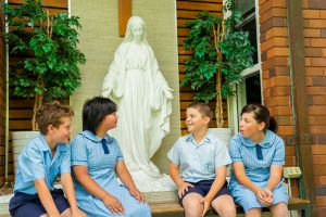 St Therese Mascot Catholic Primary School Outreach Students sitting around statue of Mary smiling