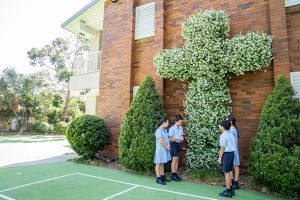 St Therese Mascot Catholic Primary School Religious Life Students in front of large flower cross