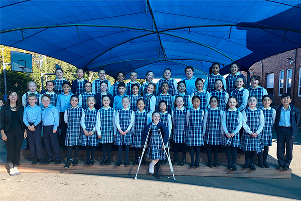 St Therese catholic Primary School Student Showcase choir students standing on outdoor stage smiling